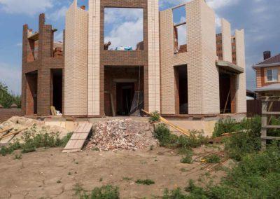 Фотография строительства дома из бежевого и коричневого кирпича